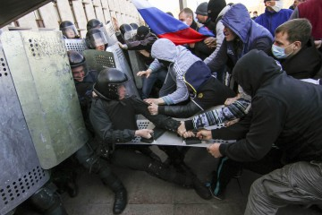 Pro-Russian protesters (R) scuffle with the police near the regional government building in Donetsk April 6, 2014. Around 100 pro-Russian protesters stormed the regional government building in the eastern Ukrainian city of Donetsk on Sunday and hung up a Russian flag in defiance of Kiev's pro-European government.  REUTERS/Stringer  (UKRAINE - Tags: POLITICS CIVIL UNREST)