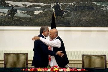 Afghanistan's presidential election candidates Abdullah Abdullah, left, and Ashraf Ghani Ahmadzai, right, hug after signing a power-sharing deal at presidential palace in Kabul, Afghanistan, Sunday, Sept. 21, 2014. Afghanistan's two presidential candidates signed a power-sharing deal Sunday, capped with a hug and a handshake, three months after a disputed runoff that threatened to plunge the country into turmoil and complicate the withdrawal of U.S. and foreign troops. (AP Photo/Massoud Hossaini)