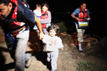 Migrants, including children run on a beach near the coastal town of Bodrum, Turkey, to board a dinghy early Tuesday, Aug. 18, 2015, in order to try to cross to the nearby Greek island of Kos. Five people have drowned off the Turkish coast as they tried to reach the Greek islands, underscoring the deadly risks of overcrowded plastic dinghies making even short crossings to Europe by people fleeing conflict in the Middle East and Africa. (AP Photo/Lefteris Pitarakis)