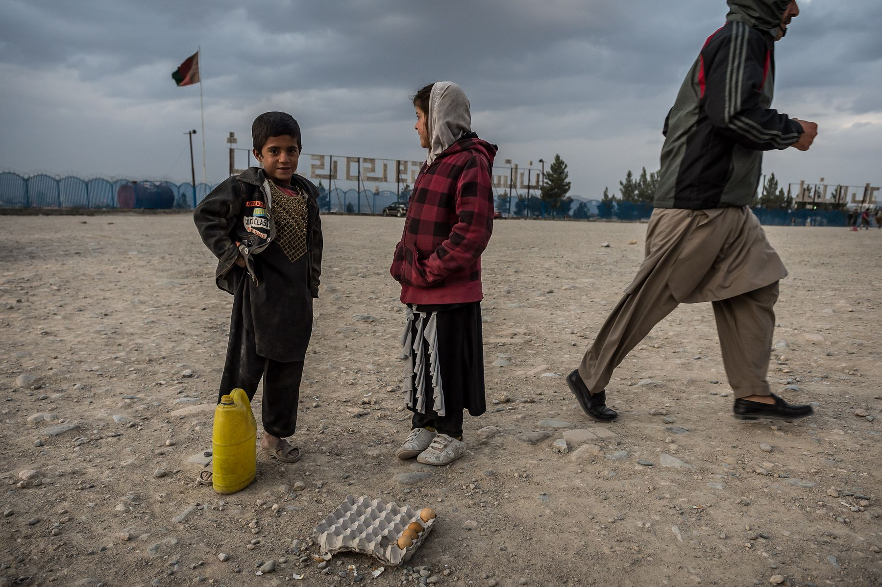 02 November 2015 - Kabul, Afghanistan. Daily life in the capital. Two young children are seen while they bag for small money in exchange to boiled eggs. The country is facing a pivotal period in its history as International armies such as US and Italy decided not to leave the country but to prolong the ongoing war against Talibans in support of the Afghan official Government.