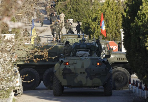 Military vehicles, believed to be Russian, are seen in front of the entrance to a military base, with Ukrainian servicemen seen in the background, in the Crimean town of Belbek near Sevastopol March 22, 2014. Russian troops have surrounded a Ukrainian airbase in Crimea and issued an ultimatum to forces inside to surrender, the deputy commander of the base in Belbek, near Sevastopol, said on Saturday. REUTERS/Vasily Fedosenko (UKRAINE - Tags: POLITICS MILITARY)