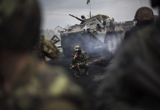 Ukrainian Army soldier smokes in front of an armoured vehicle at a burned out Pro Russia checkpoint while Pro Russia civilians block  the road to Slavyansk , in the village of Andreevka, 10 km south of Slaviansk , Ukraine, Friday, May 2, 2014.  Russia has massed tens of thousands of troops in areas near Ukraine's border. Kiev officials claim Russia is preparing to invade and that it is fomenting the unrest in the east, where insurgents have seized government buildings in about a dozen cities in towns. Moscow denies the allegations, but Foreign Minister Sergey Lavrov has warned Russia would respond to attacks on Russian citizens or interests in the east.  (AP Photo/Manu Brabo)