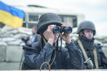 epa04192317 An Ukrainian soldier uses his binoculars at a checkpoint not far of Slaviansk, Ukraine, 05 May 2014. At least five pro-Russian activists were reported badly injured in fighting in the outskirts of the eastern Ukrainian city of Sloviansk, a rebel representative told the Interfax news agency Monday, as fighting flared anew in the troubled region. The pro-Western government in Kiev on 02 May started a fresh attempt to quash the rebellion, which it says is actively supported by Russia. Commanders say that Ukrainian army and Interior Ministry troops have fully encircled the city of more than 100,000 inhabitants.  EPA/ROMAN PILIPEY