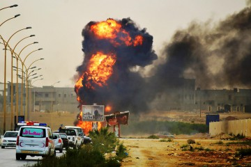 Smoke and flames rise during fighting between Islamist militias and forces loyal to a retired general Khalifa Haftar, in Benghazi, Libya, 02 June 2014.      ANSA /MAHER ALAWAMI