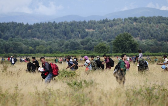 Migrants run towards Gevgelija in Macedonia after crossing Greece's border, Macedonia, August 22, 2015.Thousands of rain-soaked migrants stormed across Macedonia'Äôs border on Saturday as police lobbed stun grenades and beat them with batons, struggling to enforce a decree to stem their flow through the Balkans to western Europe. Security forces managed to contain hundreds in no-man'Äôs land. But several thousand others 'Äì many of them Syrian refugees - tore through muddy fields to Macedonian territory after days spent in the open without access to shelter, food or water.  REUTERS/Ognen Teofilovski