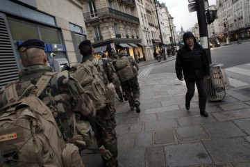 Soldiers patrol the street in Paris, Wednesday, Jan. 14, 2015. French police say as many as six members of a terrorist cell that carried out the Paris attacks may still be at large, including a man seen driving a car registered to the widow of one of the gunmen. The country has deployed 10,000 troops to protect sensitive sites, including Jewish schools and synagogues, mosques and travel hubs. (ANSA/AP Photo/Christophe Ena)