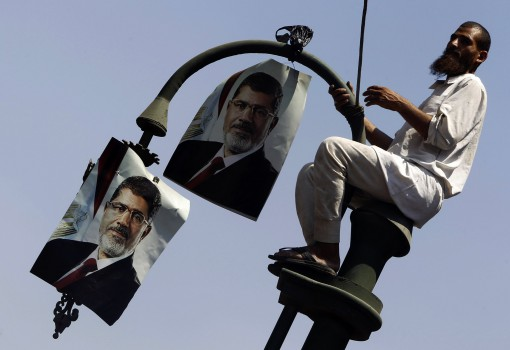 A member of the Muslim Brotherhood and supporter of ousted Egyptian President Mohamed Mursi places posters of Mursi on a lamp post during a protest in front of the courthouse and the Attorney General's office in Cairo July 22, 2013. The family of ousted Egyptian President Mohamed Mursi said on Monday it would take legal action against the army, accusing it of abducting the country's first democratically-elected president. REUTERS/Amr Abdallah Dalsh  (EGYPT - Tags: POLITICS CIVIL UNREST RELIGION)
