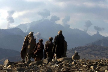 Anti-Taliban Afghan fighters watch several explosions from U.S. bombings in the Tora Bora mountains in Afghanistan December 16, 2001. REUTERS/Erik de Castro