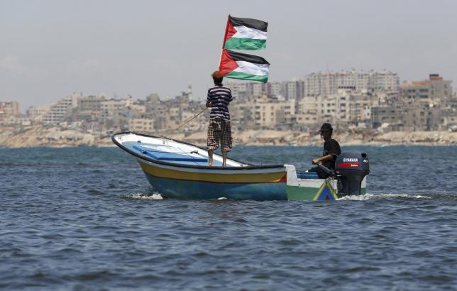 A Palestinian man riding a boat holds Palestinian flags during a protest against the Israeli blocking of a boat of foreign activists from reaching Gaza, at the Seaport of Gaza City June 29, 2015. REUTERS/Suhaib Salem