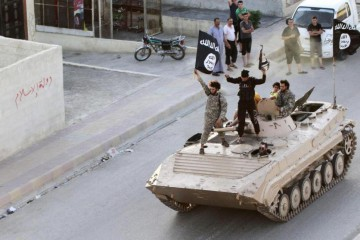 Militant Islamist fighters take part in a military parade along the streets of northern Raqqa province, June 30, 2014.  REUTERS/Stringer