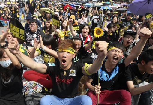 "Demonstrators shout slogans in front of the Presidential Office in Taipei March 30, 2014. Thousands of demonstrators marched the streets to protest against the controversial trade pact with mainland China. The Chinese characters read, ""Defend democracy; Reject the trade pact."" REUTERS/Toby Chang  (TAIWAN - Tags: POLITICS CIVIL UNREST)"