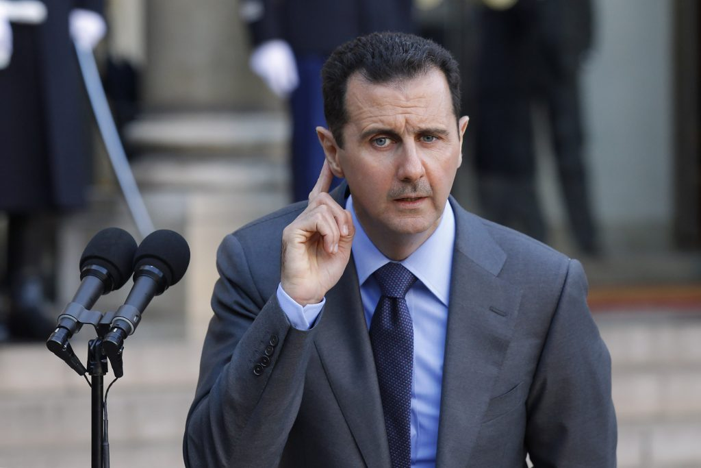 Syria's President Bashar al-Assad answers journalists after a meeting at the Elysee Palace in Paris, December 9, 2010. REUTERS/Benoit Tessier (FRANCE - Tags: POLITICS)