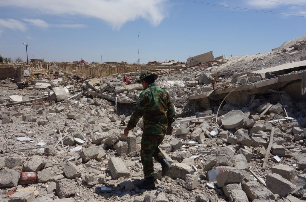 One of our Kurdish Peshmerga escorts picks his way through the ruins of Telskuf