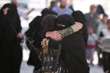 A woman embraces a Syria Democratic Forces (SDF) fighter after she was evacuated with others by the SDF from an Islamic State-controlled neighbourhood of Manbij, in Aleppo Governorate, Syria, August 12, 2016. The SDF has said Islamic State was using civilians as human shields. REUTERS/Rodi Said