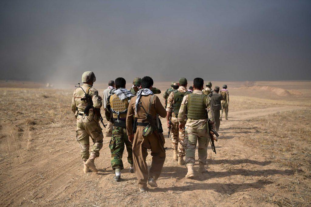 Soldati peshmerga camminano attraversano la prima linea del fronte contro le bandiere nere dell'Isis