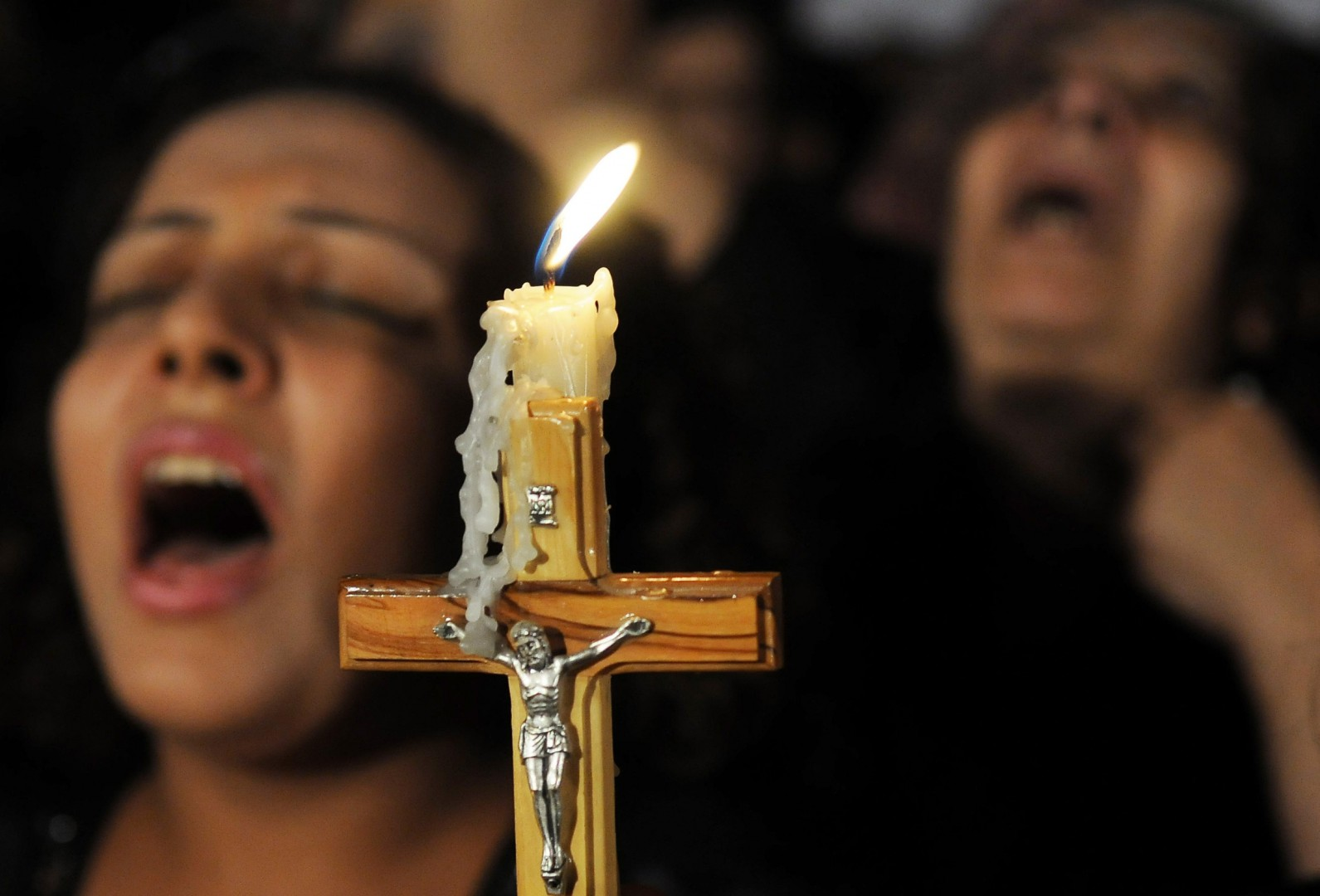 Coptic Christians carry a crucifix and chant prayers during a candlelight protest at Abassaiya Orthodox Cathedral in Cairo Oct. 16, one week after people were killed during clashes with soldiers and riot police. At least 26 people, mostly Christians, were killed Oct. 9 when troops broke up a peaceful protest against an earlier attack on a church in southern Egypt. (CNS photo/stringer via Reuters) (Oct. 18, 2011) See EGYPT-CHRISTIANS Oct. 10, 2011.