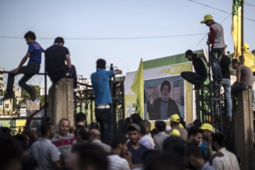 epa04765813 Hezbollah supporters listen to a speech by the Secretary General of Hezbollah, Hassan Nasrallah (on screen), during a rally celebrating the 15th anniversary of the Israeli withdrawal from south Lebanon in Nabatiyeh, south Lebanon, 24 May 2015. According to reports, during his speech he likened the situation pertaining to the group calling themselves the Islamic State (IS) to that of the Israeli invasion of Lebanon in 1982, which divided people.  EPA/OLIVER WEIKEN