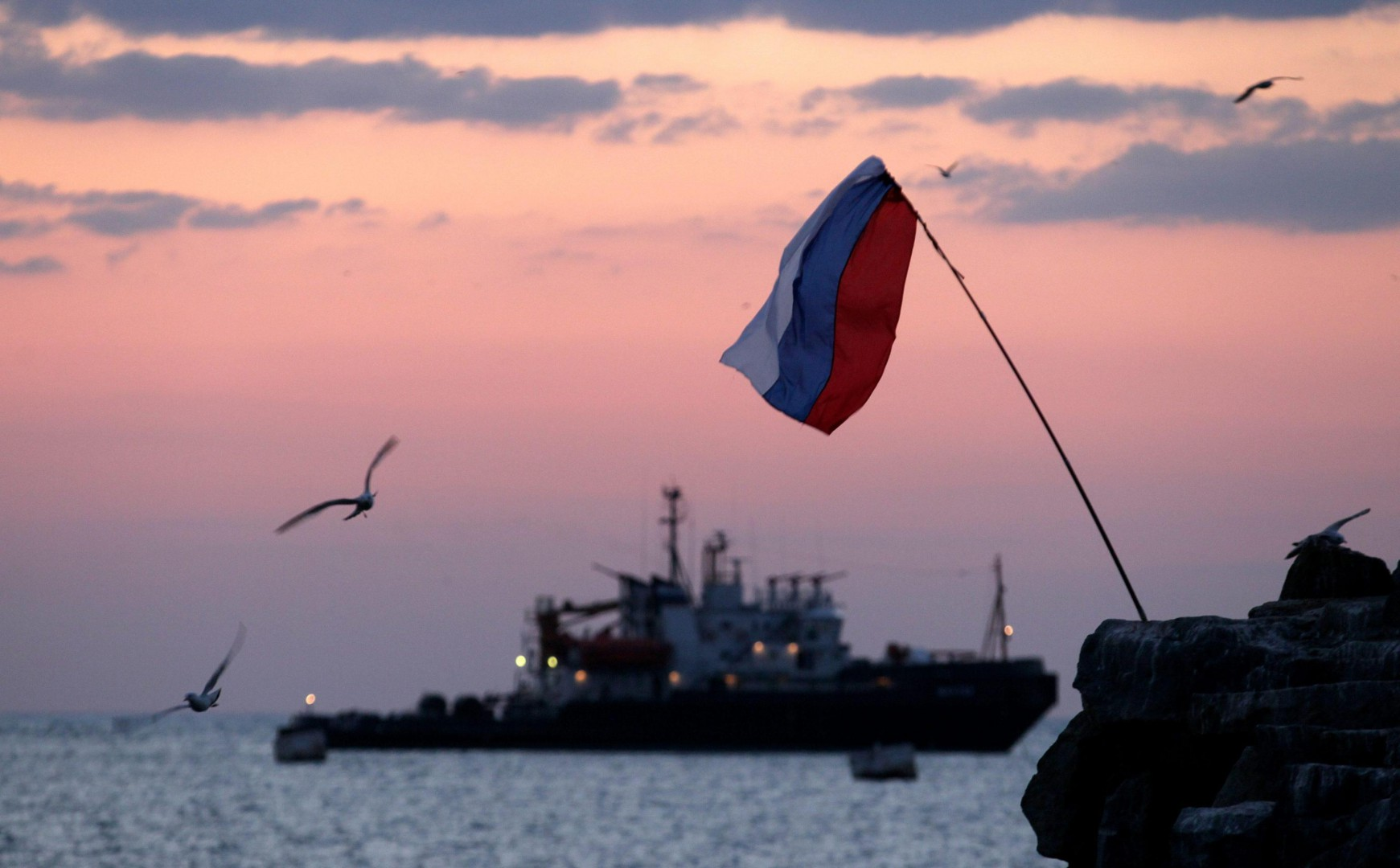 epa04122006 A Russian national flag waves in the bay of Seavastopol, Crimea, Ukraine, 12 March 2014. Crimea's secessionist authorities said on 12 March that they have partially closed the region's airspace to 'keep out provocateurs' in the run-up to the March 16 referendum about joining Russia.  EPA/ZURAB KURTSIKIDZE