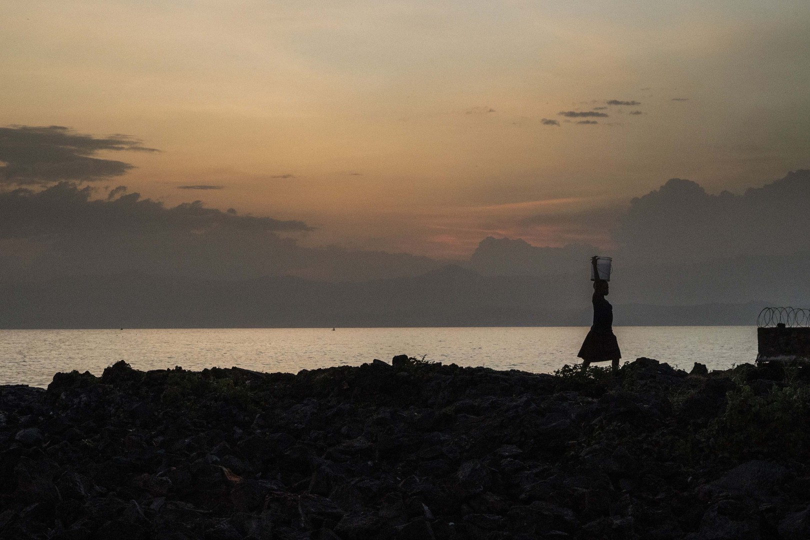 Africa, Democratic Republic of Congo, North Kivu, Goma. 24/01/2017. A landscape of the Kivu Lake at the sunset. Women are a driver for Congolese society, because it is the women who perform the most varied tasks in order to support their families, and they are also responsible for raising children. More often than not, rape goes unpunished in the Congo. Rape victims totalled 15,000 in 2015 alone.