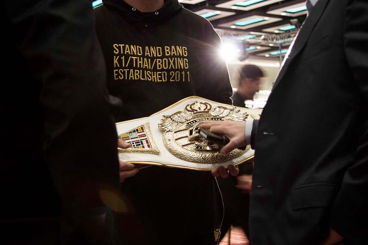 Gli organizzatori di un evento MMA osservano una cintura destinata a uno dei vincitori.