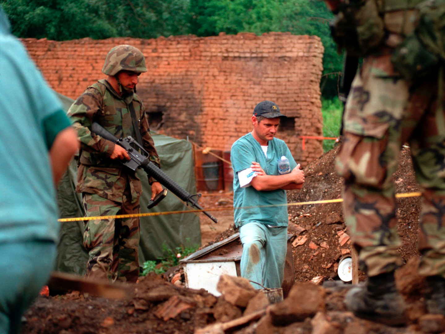 990701-M-5696S-003 	U.S. Marines provide security as members of the Royal Canadian Mounted Police Forensics Team investigate a grave site in a village in Kosovo on July 1, 1999.  Elements of the 26th Marine Expeditionary Unit are deployed from ships of the USS Kearsarge Amphibious Ready Group as an enabling force for KFOR.  KFOR is the NATO-led, international military force which will deploy into Kosovo on a peacekeeping mission known as Operation Joint Guardian.  KFOR will ultimately consist of over 50,000 troops from more than 24 contributing nations, including NATO member-states, Partnership for Peace nations and others.  DoD photo by Sgt. Craig J. Shell, U.S. Marine Corps.  (Released)