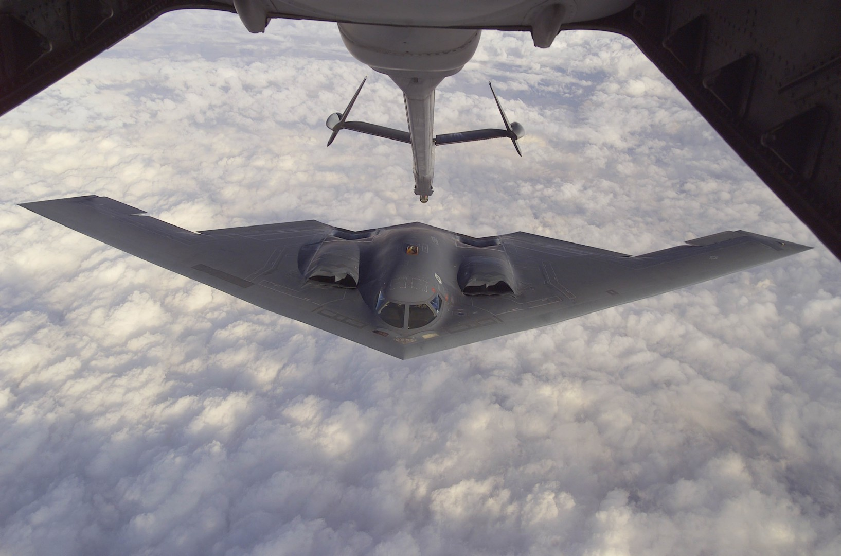 """The B-2 Spirit approaches the boom of a McGuire Air Force Base, New Jersey KC-10A Extender during a Capstone orientation flight. Capstone is a Joint Airborne/Air Transportability Training mission providing interservice training for the wartime application of airlift. Through Capstone, senior level officers are able to observe the significance of airlift and its role in all military operations. The B-2 Spirit is a multi-role bomber capable of delivering both conventional and nuclear munitions. It is a dramatic leap forward in technology and represents a major milestone in the U.S. bomber modernization program. The B-2 brings massive firepower to bear, in a short time, anywhere on the globe through previously impenetrable defenses. The B-2 provides the penetrating flexibility and effectiveness inherent in manned bombers. Its low-observable, or """"stealth,"""" characteristics give it the unique ability to penetrate an enemy's most sophisticated defenses and threaten its most valued, and heavily defended, targets. The B-2's low-observability provides it greater freedom of action at high altitudes, thus increasing its range and a better field of view for the aircraft's sensors. Its capability to penetrate air defenses and threaten effective retaliation provide a strong, effective deterrent and combat force well through the 21st century. The aerial refueling took place aboard a McGuire AFB, New Jersey KC-10A Extender on October 5, 2000. (U.S. Air Force photo by Staff Sgt. Scott H. Spitzer)"""