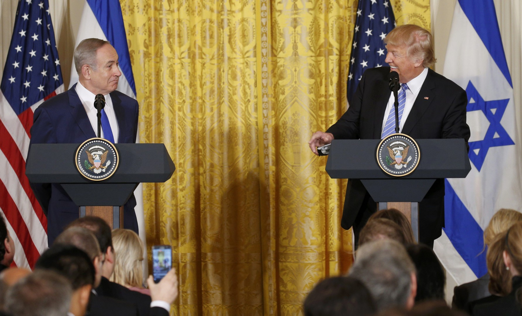 U.S. President Donald Trump (R) looks to Israeli Prime Minister Benjamin Netanyahu hold a joint news conference at the White House in Washington, U.S., February 15, 2017.   REUTERS/Kevin Lamarque