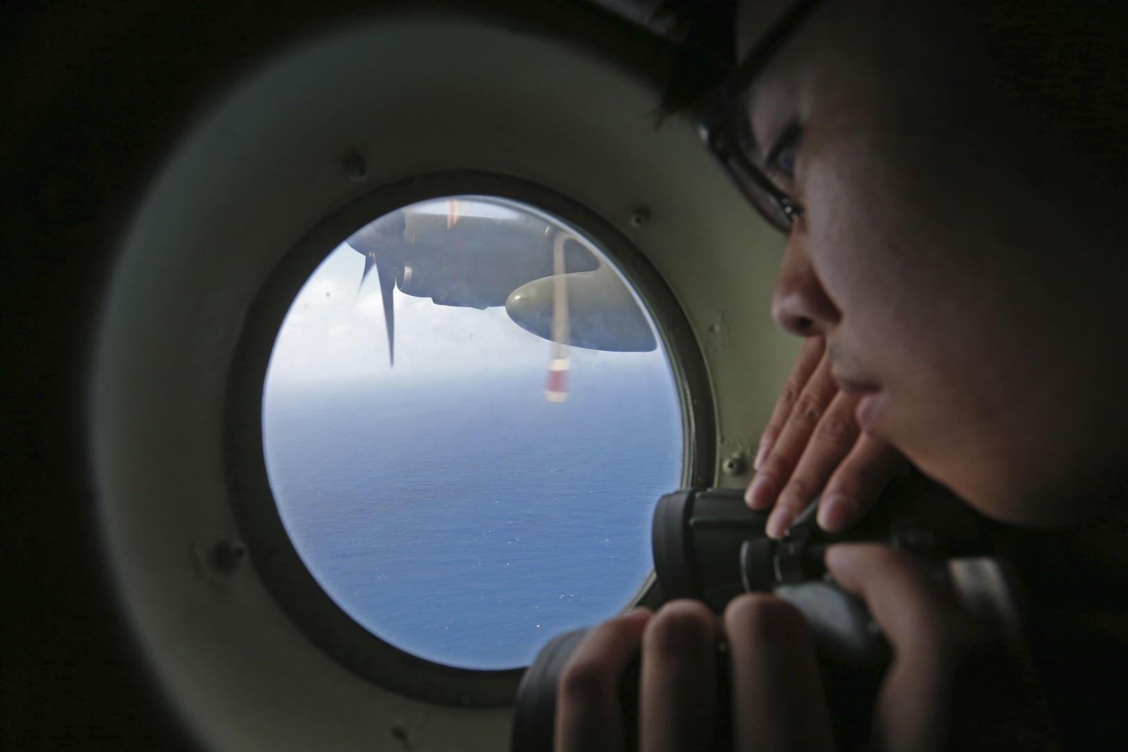 A member of the military personnel looks out of a Republic of Singapore Air Force (RSAF) C130 transport plane during a search for the missing Malaysia Airlines MH370 plane over the South China Sea March 11, 2014. REUTERS/Thong Kah Hoong Dennis/Lianhe Zaobao/Singapore Press Holdings Ltd    (DISASTER TRANSPORT MILITARY) ATTENTION EDITORS - THIS IMAGE HAS BEEN SUPPLIED BY A THIRD PARTY. FOR EDITORIAL USE ONLY. NOT FOR SALE FOR MARKETING OR ADVERTISING CAMPAIGNS. NO SALES. NO ARCHIVES. NO ONLINE USE. NOT FOR SALE FOR INTERNET DISPLAY.  IT IS DISTRIBUTED, EXACTLY AS RECEIVED BY REUTERS, AS A SERVICE TO CLIENTS. TEMPLATE OUT. SINGAPORE OUT. NO COMMERCIAL OR EDITORIAL SALES IN SINGAPORE