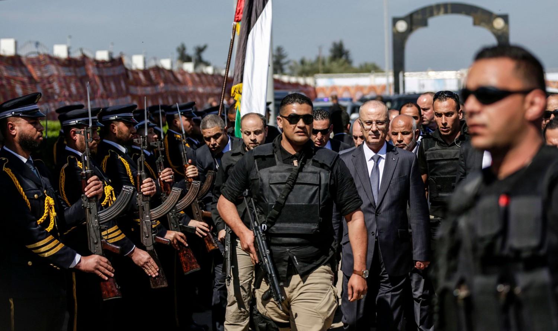 Il primo ministro palestinese Rami Hamdallah scortato dalle sue guardie del corpo. AFP PHOTO / MAHMUD HAMS