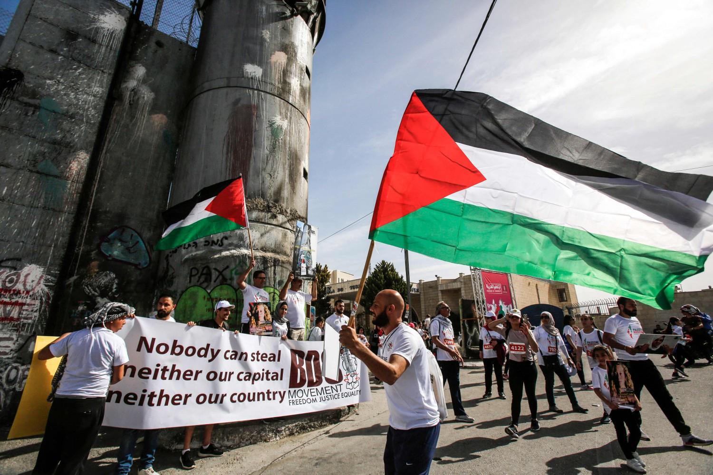 Una bandiera palestinese in mano a un corridore alla Maratona di Palestina