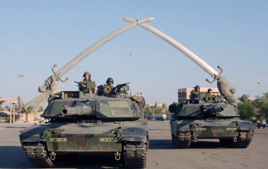 """US Army (USA) M1A1 Abrams MBT (Main Battle Tank), and personnel from A Company (CO), Task Force 1st Battalion, 35th Armor Regiment (1-35 Armor), 2nd Brigade Combat Team (BCT), 1st Armored Division (AD), pose for a photo under the """"Hands of Victory"""" in Ceremony Square, Baghdad, Iraq during Operation IRAQI FREEDOM. The Hands of Victory monument built at the end of the Iran-Iraq war marks the entrance to a large parade ground in central Baghdad. The hand and arm are modeled after former dictator Saddam HusseinÕs own and surrounded with thousands of Iranian helmets taken from the battlefield. The swords made for the guns of dead Iraqi soldiers, melted and recast into the 24-ton blades."""