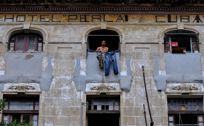 Un uomo stende i panni fuori dalla sua casa a L'Havana mentre Miguel Diaz-Canel viene nominato nuovo presidente di Cuba (LaPresse)