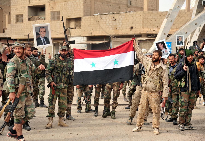 Soldati siriani espongono la bandiera nazionale e i ritratti di Hafez e Bashar al Assad (LaPresse)