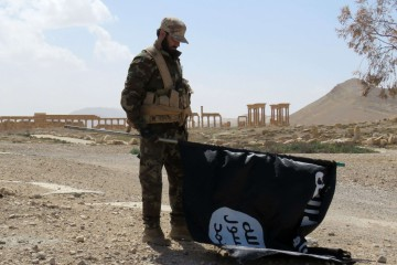 Un soldato siriano impugna la bandiera dell'Isis dopo aver sconfitto i jihadisti a Palmira (LaPresse)