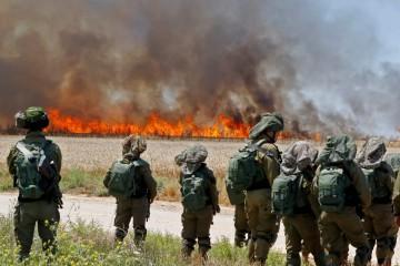I soldati israeliani osservano il fuoco dopo che le violenze sono infuriate in tutta la Striscia di Gaza