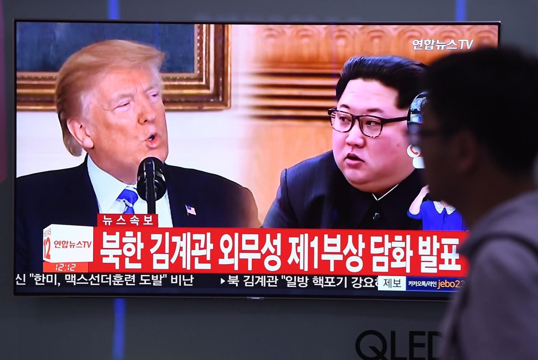 Un uomo passeggia alla stazione di Seul mentre osserva in tv i due leader