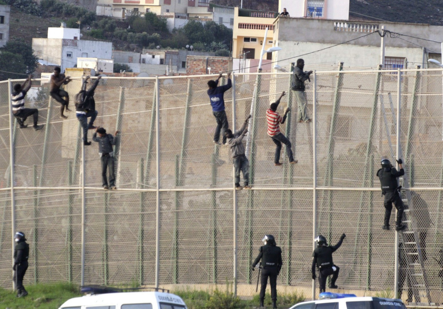 Policemen watch a group of Sub-saharan immigrants who climbed the fence at the border between Morocco and Melilla, the Spanish enclave on the north of Africa, in another mass attempt to enter Melilla, 15 october 2014. Some 200 immigrants tried to cross into Melilla. EFE/F. G. Guerrero