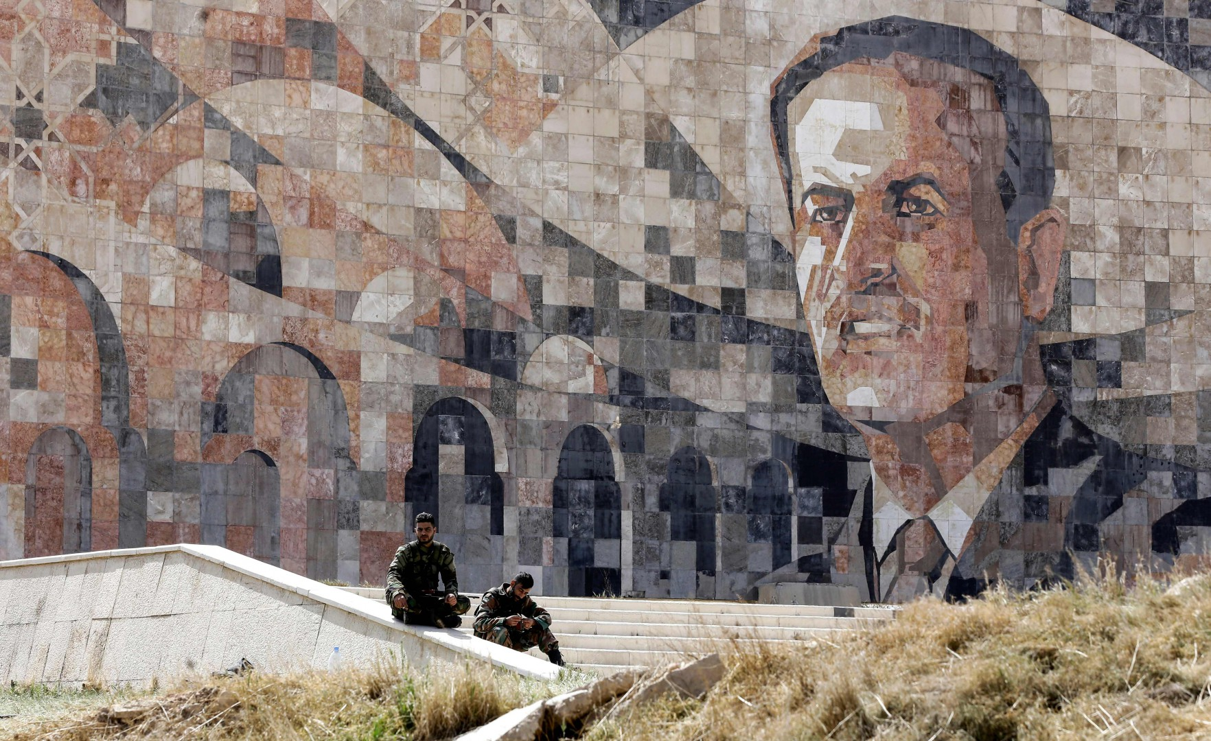 Syrian regime forces sit by a marble mosaic monument depicting a picture of late President Hafez al-Assad, at the entrance of Harasta in Eastern Ghouta on the outskirts of Damascus on March 25, 2018, after a deal was struck with rebels in the area to evacuate the town. Syrian rebels and civilians gathered in rubble-strewn streets, awaiting evacuation from the penultimate opposition-held pocket of Eastern Ghouta. Faylaq al-Rahman, the Islamist rebel group that controls the area, agreed to pull out in exchange for an end to nearly five weeks of devastating bombardment by the government and its allies.   / AFP PHOTO / LOUAI BESHARA