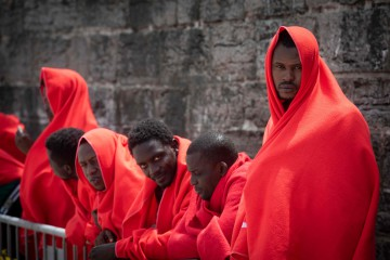 Migrants wait to be assisted by the Spanish Red Cross at the Port of Tarifa, southern Spain, on June 23, 2018.  A total of 418 migrants were rescued in three operations off the coast of Spain on Saturday, the national rescue service said. / AFP PHOTO / MARCOS MORENO