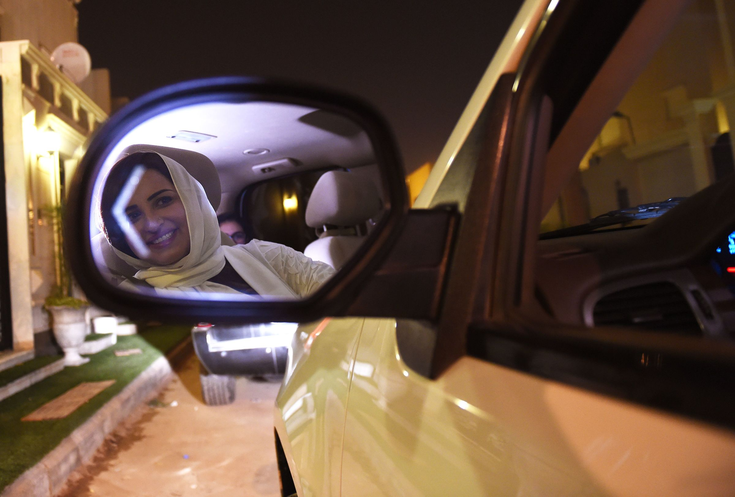 Saudi Samar Al-Moqren is seen in her car's rear-view mirror as she drives through Riyadh city's streets for the first time just after midnight, June 24, 2018, when the law allowing women to drive took effect.  Saudi Arabia will allow women to drive from June 24, ending the world's only ban on female motorists, a historic reform marred by what rights groups call an expanding crackdown on activists.  / AFP PHOTO / FAYEZ NURELDINE