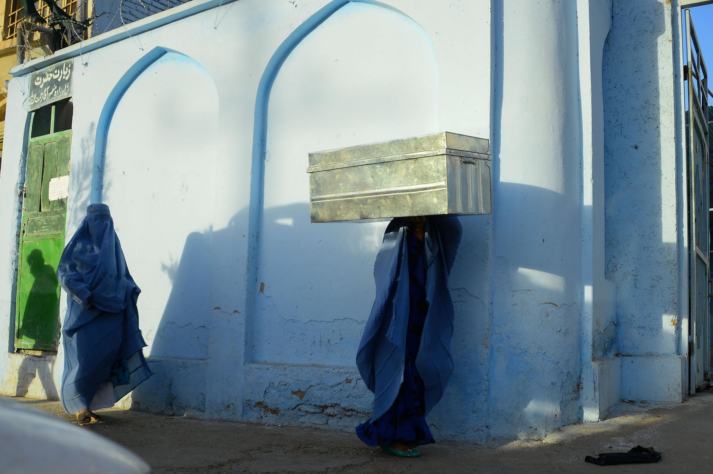 Due donne con il burqa attraversano le strade di Herat in Afghanistan (LaPresse)