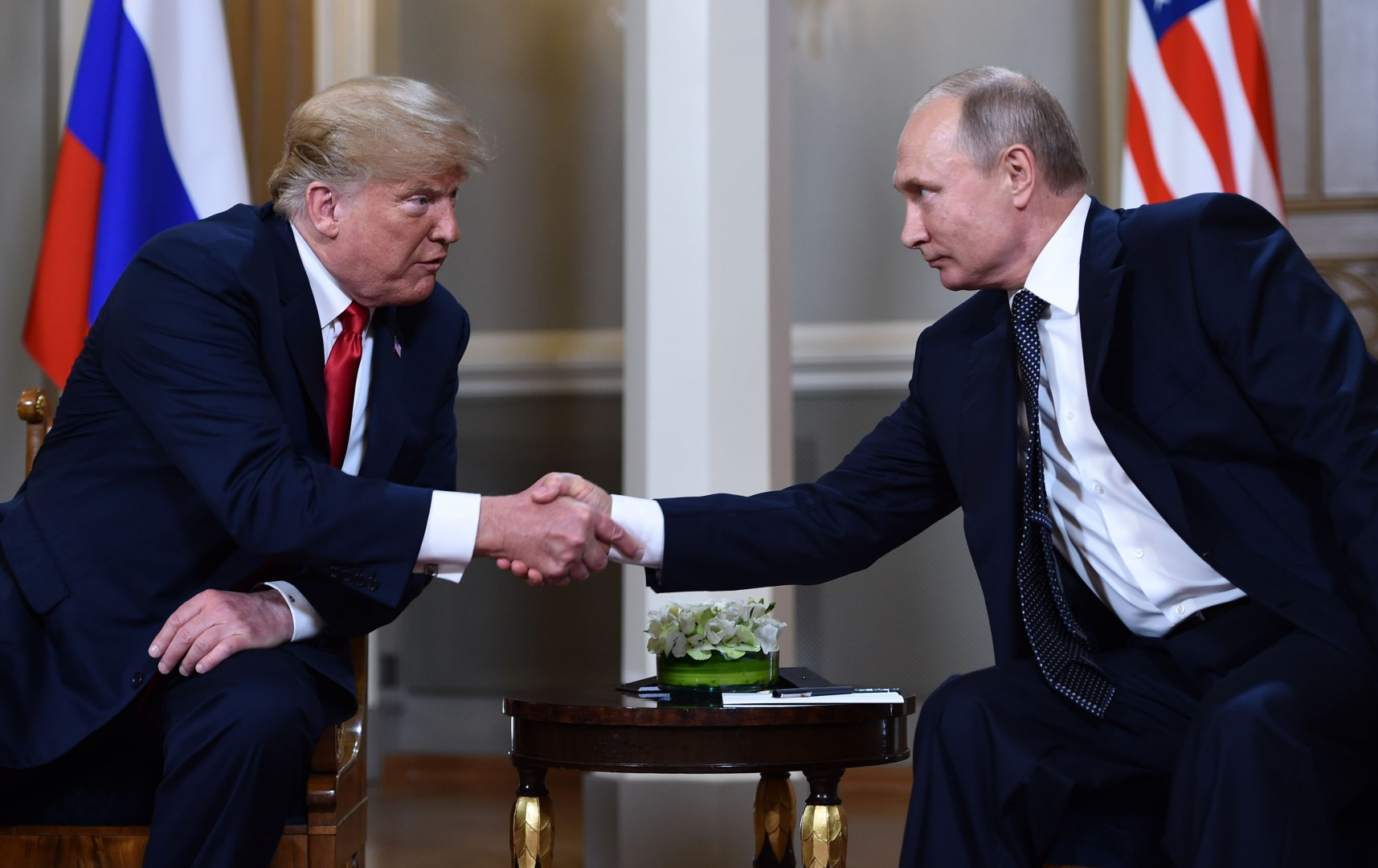 Russian President Vladimir Putin (R) and US President Donald Trump shake hands before a meeting in Helsinki, on July 16, 2018. / AFP PHOTO / Brendan Smialowski
