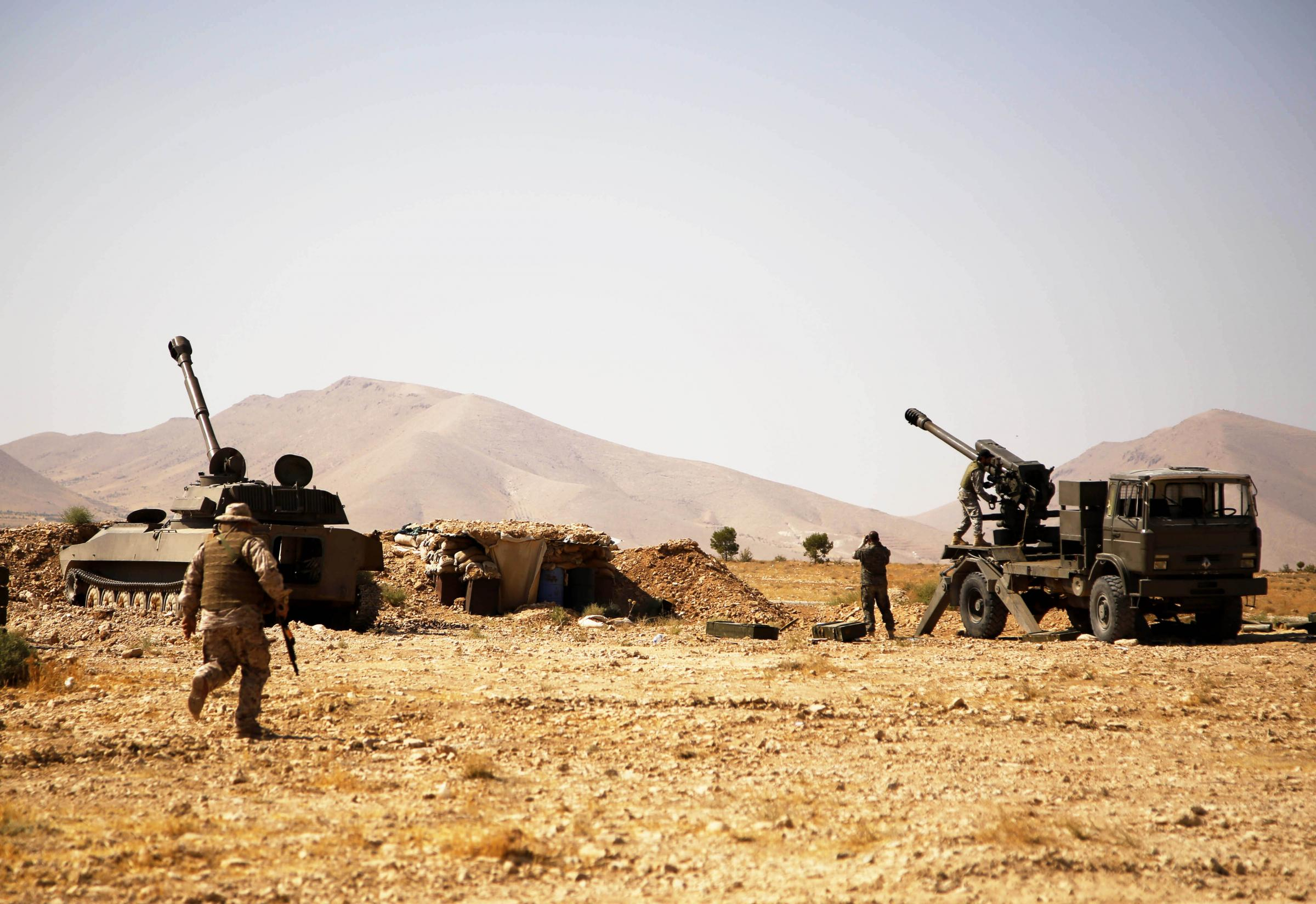 (170823) -- QARA(SYRIA), Aug.23 (Xinhua) -- Fighters of the Lebanese Hezbollah group prepare to fire artillery shells on the positions of the Islamic State (IS) militants in Qara town, western Qalamoun region, Syria, on Aug. 23, 2017. The Lebanese Hezbollah group and Syrian army are dealing heavy blow to the Islamic State (IS) group in Syria's Qalamoun region near Lebanon to end the presence of the terror-designated group in the border region between both countries. (Xinhua/Ammar Safarjalani)