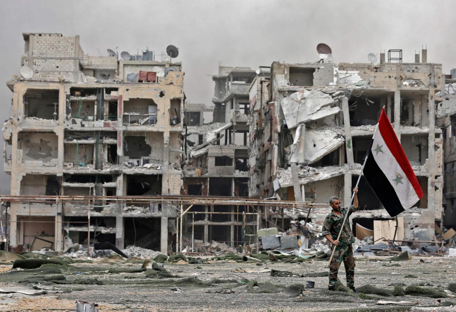 Uno soldato di Assad issa la bandiera governativa nel campo profughi di Yarmouk (LaPresse)