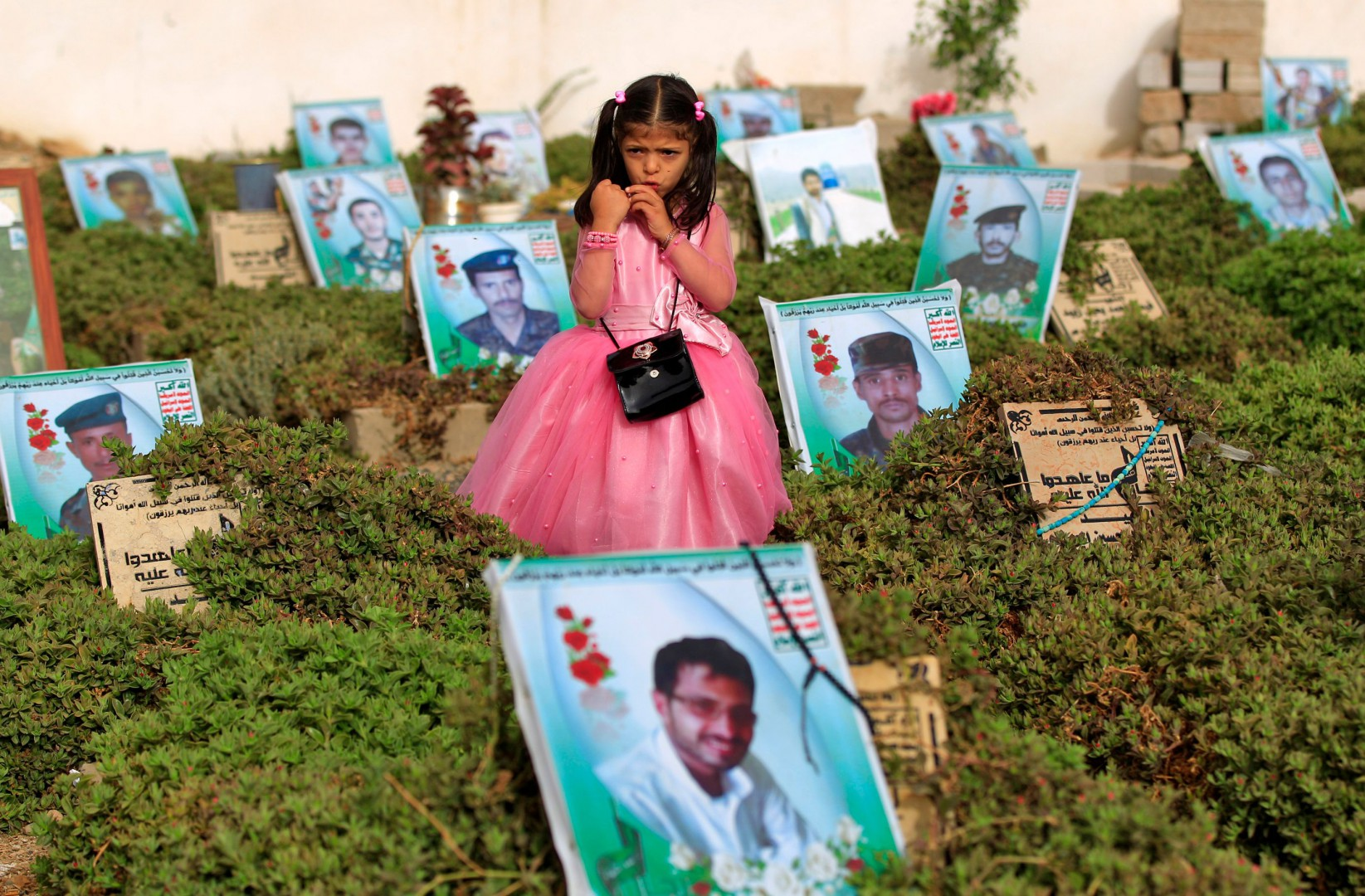 TOPSHOT - EDITORS NOTE: Graphic content / A Yemeni girl stands near the grave of a relative in a cemetery in the capital Sana'a on June 15, 2018. Muslims worldwide celebrate Eid al-Fitr marking the end of the fasting month of Ramadan. / AFP PHOTO / Mohammed HUWAIS