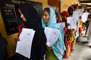 India. delle donne mostrano il loro certificato di ingresso nel Paese (LaPresse)