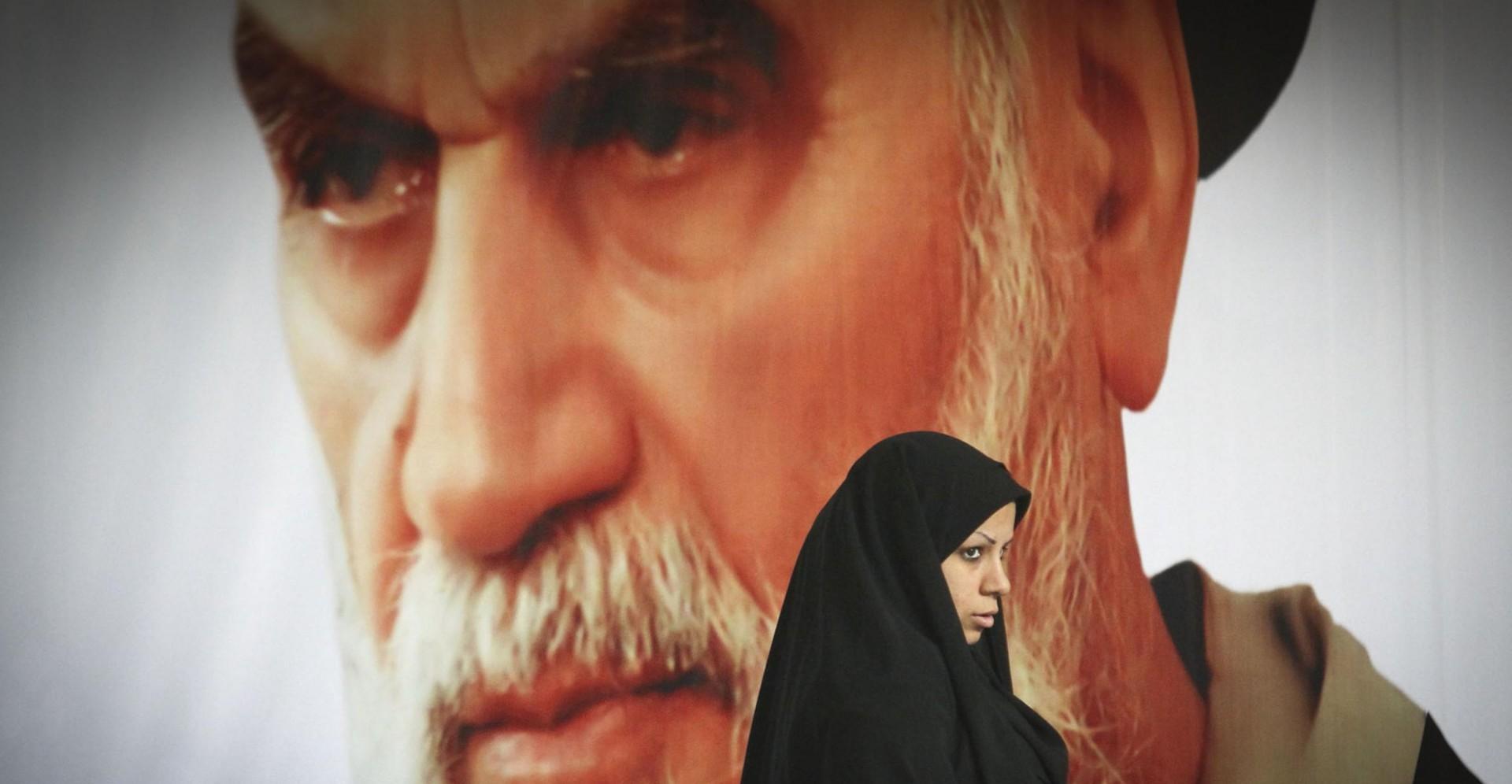 Una donna cammina in Iran davanti al ritratto dell'imam Khomeini (LaPresse)