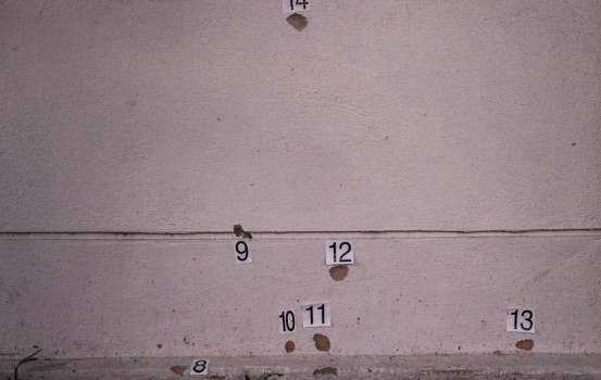 Numbered markers are seen on a bullet-riddled wall at the scene where Palestinian scientist Fadi Mohammad al-Batsh was gunned down April 21 in what his family claim was an assassination by Israel's Mossad spy agency, in Kuala Lumpur on April 22, 2018. Malaysian police said Fadi Mohammad al-Batsh, 35, was killed in a drive-by motorcycle shooting as he headed on foot to take part in dawn Muslim prayers on April 21. / AFP PHOTO / Mohd RASFAN