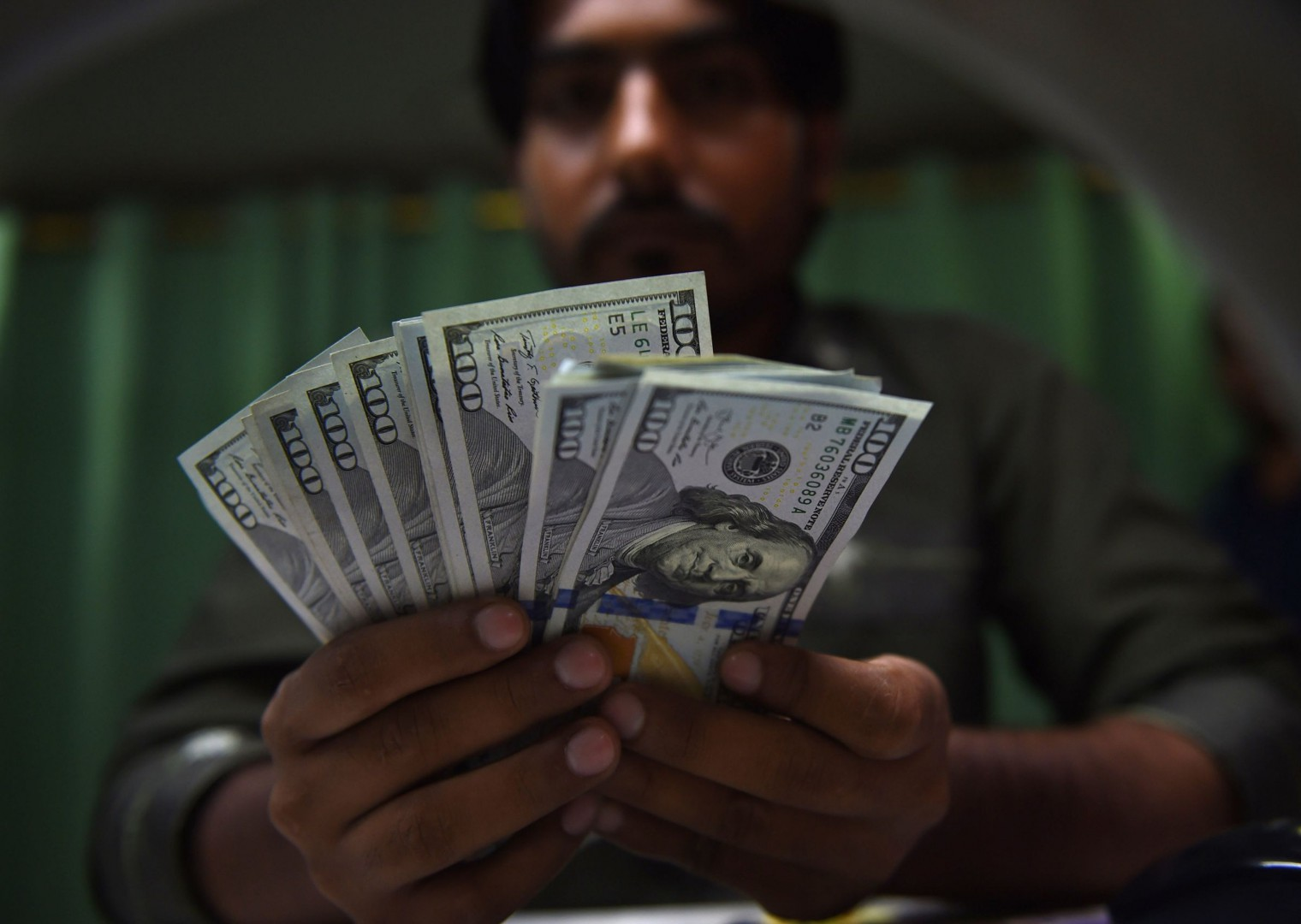 This photo taken on July 17, 2018 shows a Pakistani currency dealer counting US dollars banknotes at a currency exchange shop in Karachi. Pakistan's next government faces growing fears of a balance of payments crisis, with speculation mounting it will have to seek its second IMF bailout in five years. The central bank is burning through foreign reserves and devaluing the rupee, including another five-percent dive this week, in a bid to bridge a widening trade deficit. / AFP PHOTO / RIZWAN TABASSUM / TO GO WITH Pakistan-election,POINTS