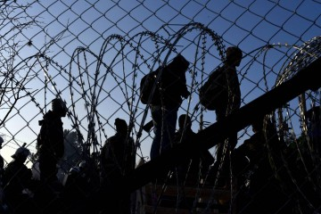 (160224) -- SKOPJE, Feb. 24, 2016 (Xinhua) -- Afghan migrants protest and stand behind the wire fencing at the closed Greek-Macedonian border, near the Macedonian city of Gevgelija on Feb. 23, 2016. Macedonia has confirmed that it only allowed Syrian and Iraqi refugees through, matching a decision by its northern neighbor, Serbia. Around 5,000 migrants were waiting at the border wishing to continue their journey across Macedonia, Serbia, Croatia, Slovenia and then Austria, with Germany the final goal for most. (Xinhua)